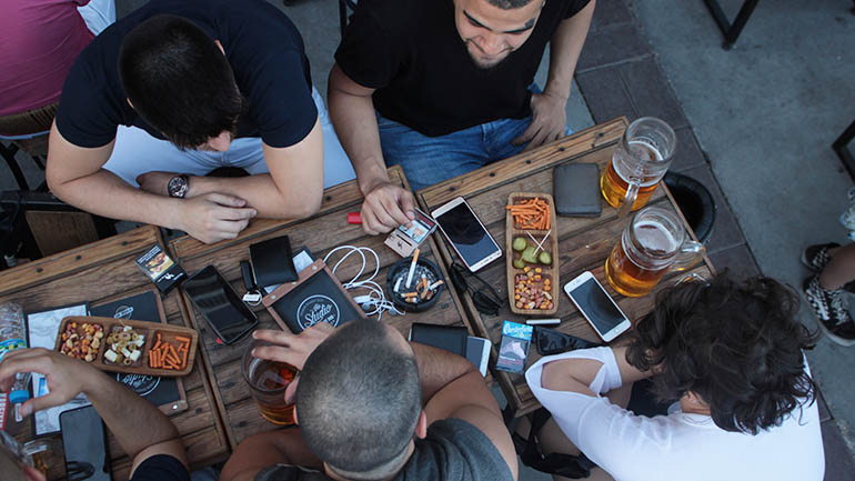 Marketing to millennials - people around a table with phones out