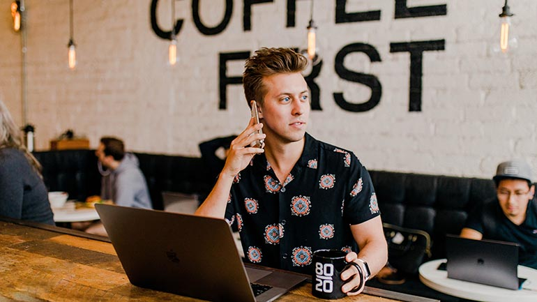 Marketing to millennials - young man in coffee shop on phone